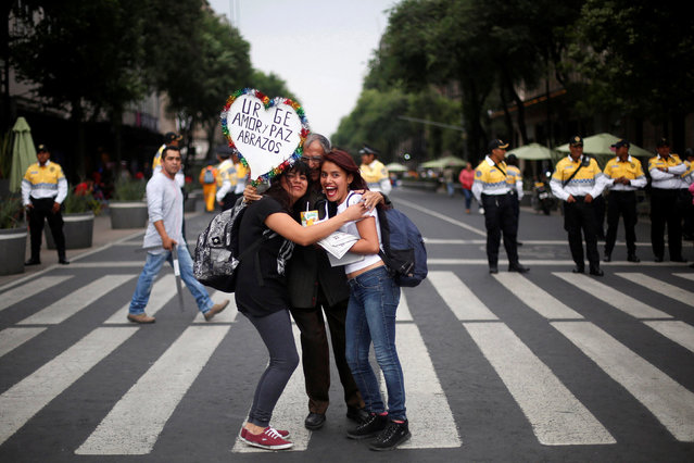 """A demonstrator embraces two women during a march in commemoration of the 45th anniversary of the Halconazo, when a Mexican paramilitary unit called the Halcones (Falcons) killed an unknown number of students during a demonstration in 1971, in Mexico City, Mexico, June 10, 2016. The sign reads """"Urge love and peace. Hugs"""". (Photo by Edgard Garrido/Reuters)"""