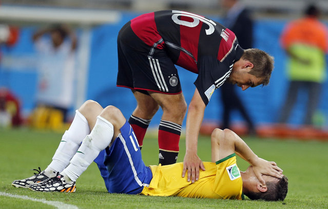 Brazil's Oscar, bottom, is comforted by Germany's Philipp Lahm during the World Cup semifinal soccer match between Brazil and Germany at the Mineirao Stadium in Belo Horizonte, Brazil, Tuesday, July 8, 2014. Germany beat Brazil 7-1 and advanced to the final. (Photo by Frank Augstein/AP Photo)