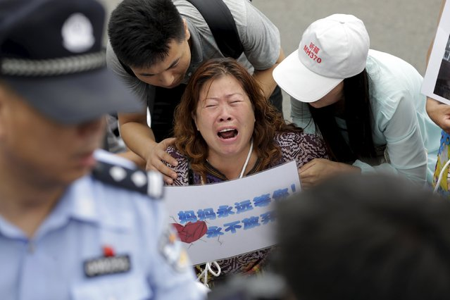 "A woman whose relative was aboard Malaysia Airlines flight MH370, holds a placard that reads, ""Mom is always here waiting for you, never will give up"", as she cries next to family members and kneels down in front of media ahead of a briefing given by Malaysia Airlines, in Beijing August 7, 2015. (Photo by Jason Lee/Reuters)"