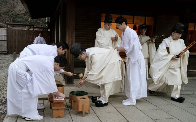 A shinto musician is assisted by his colleagues to purify himself prior to a ritual to mark the end of the year and prepare for the new one at Meiji Shrine in Tokyo, Japan, 31 December 2019. About three million people visit the shrine during the first three days of the year to pray for their health, prosperity, happiness and world peace. (Photo by Kimimasa Mayama/EPA/EFE/Rex Features/Shutterstock)