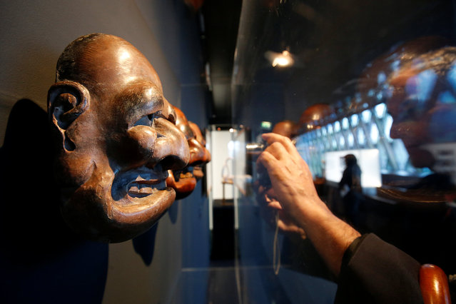 "A visitor takes a picture of a Bugaku Japanese mask (18eme) from traditional Kyogen comic theatre that is displayed during the exhibition ""Jacques Chirac ou le dialogue des cultures"" at the Musee du quai Branly in Paris, France, June 20, 2016. This major exhibition is devoted to former French President Chirac, the Quai Branly Museum founder, who was passionate about non-European arts and different civilizations. (Photo by Jacky Naegelen/Reuters)"