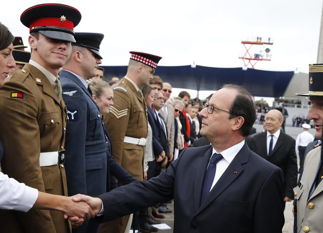 French President Francois Hollande (R) shakes hand with military personnel  after the traditional military parade as part of the Bastille Day celebrations in Paris, France, 14 July 2014. (Photo by Etienne Laurent/EPA)