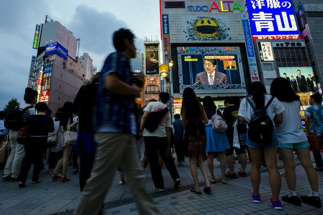 """People watch Japan's Prime Minister Shinzo Abe on a screen as he gives a statement in Tokyo August 14, 2015. Prime Minister Shinzo Abe, in a statement marking the 70th anniversary of World War Two's end, acknowledged Japan had inflicted """"immeasurable damage and suffering"""" on innocent people but said generations not involved in the conflict should not be burdened with continued apologies. (Photo by Thomas Peter/Reuters)"""