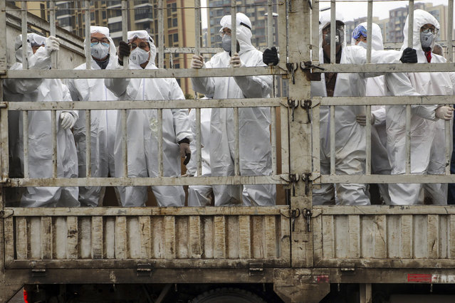 In this Thursday, February 6, 2020, photo, workers in protective suits ride on a truck carrying medical supplies into Huoshenshan temporary hospital built for patients who diagnosed with 2019-nCoV in Wuhan in central China's Hubei province. The number of confirmed cases of the new virus has risen again in China on Saturday as the ruling Communist Party faced anger and recriminations from the public over the death of a doctor who was threatened by police after trying to sound the alarm about the disease over a month ago. (Photo by Chinatopix via AP Photo)