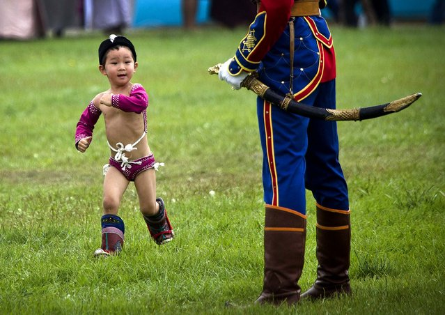 A  boy in costume runs past a member of the honor guard during the Naadam Festival in Ulan Bator on July 11, 2012