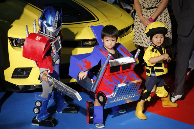 """Children dressed in Transformers costume pose for photos during the Japan premiere of the movie """"Transformers: Age of Extinction"""" in Tokyo July 28, 2014. The movie will open in Japan on August 8, 2014. (Photo by Toru Hanai/Reuters)"""