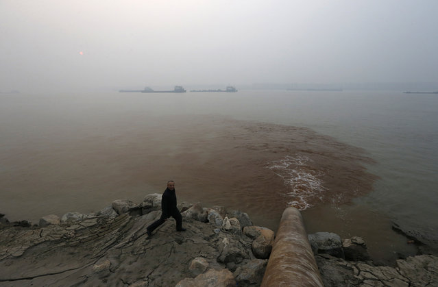 A man walks by a pipe discharging waste water into the Yangtze River from a paper mill in Anqing, Anhui province, December 4, 2013. (Photo by William Hong/Reuters)