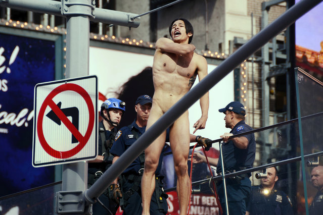 A naked man shouts before jumping from the ledge above the TKTS Broadway ticket booth in New York's Times Square, Thursday, June 30, 2016. Police said the man, who was shouting about presumptive Republican presidential nominee Donald Trump, was conscious after the jump of about 16 feet off the booth. (Photo by AP Photo)