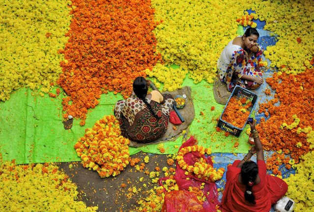 Vendors sit at a flower market in the southern Indian city of Bangalore August 7, 2014. (Photo by Abhishek N. Chinnappa/Reuters)