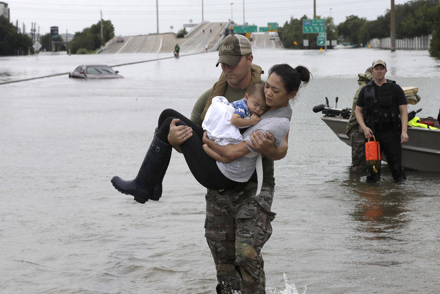 Houston Police SWAT officer Daryl Hudeck carries Catherine Pham and her 13-month-old son Aiden after rescuing them from their home surrounded by floodwaters from Tropical Storm Harvey Sunday, August 27, 2017, in Houston. The remnants of Hurricane Harvey sent devastating floods pouring into Houston Sunday as rising water chased thousands of people to rooftops or higher ground. (Photo by David J. Phillip/AP Photo)