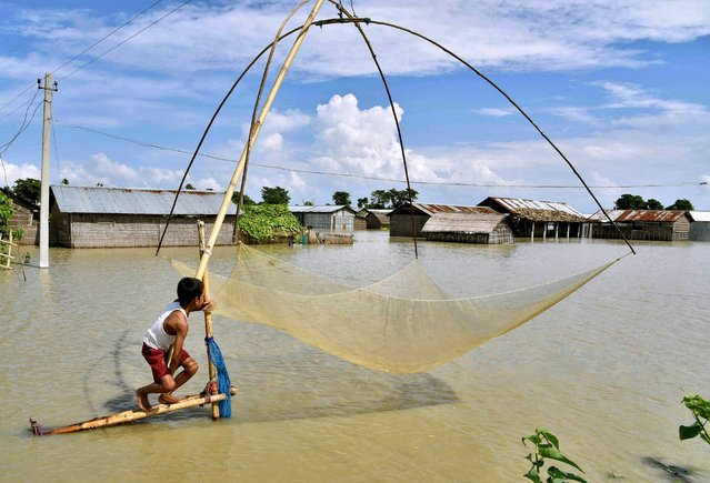 A boy prepares to cast a fishing net in the flood waters next to submerged houses after heavy rains at Patekibari village in Marigaon district in Assam, India, August 23, 2015. Four people have died and over 500,000 people have been affected by the floods caused by heavy rains in the state, according to an official media release. (Photo by Reuters/Stringer)