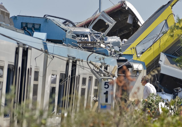 A man watches the scene of a train accident after two commuter trains collided head-on near the town of Andria, in the southern region of Puglia, killing several people, Tuesday, July 12, 2016. (Photo by Gaetano Lo Porto/AP Photo)