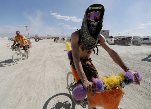 Burning Man participant Rafie bikes through the Burning Man arts and music festival in the Black Rock Desert of Nevada, U.S. August 29, 2017. (Photo by Jim Urquhart/Reuters)