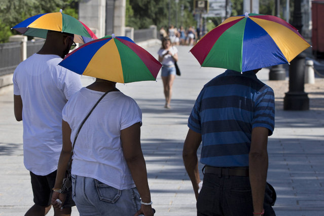 Tourists protect themselves from the sun with sun umbrellas in Madrid, Spain, Thursday, August 3, 2017. The regional Madrid government has put out a maximum level 2 alert regarding high temperatures in Madrid, recommending that people shouldn't go outside during the hottest period of the day without adequate protecting as temperatures in Madrid are expected to reach 38 degrees centigrade or higher (100.4 degrees Fahrenheit) on Friday. (Photo by Paul White/AP Photo)