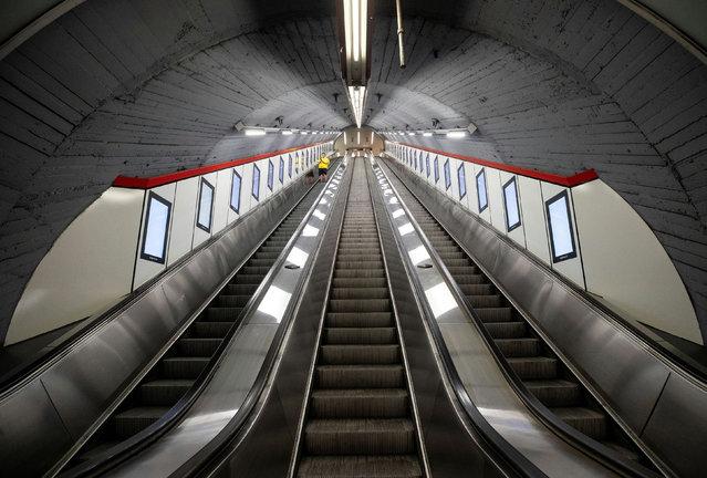 "A man rides an escalator at ""Karlsplatz"" underground station during the coronavirus disease (COVID-19) outbreak in Vienna, Austria on March 19, 2020. (Photo by Lisi Niesner/Reuters)"