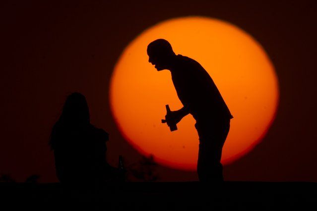 A man drinks a beer next to a woman during sunset in Brasilia, August 15, 2014. (Photo by Ueslei Marcelino/Reuters)