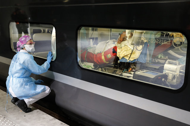 A medical staff watches from a platform of the Gare d'Austerlitz train station on April 1, 2020 in Paris through the window of a medicalised TGV high speed trains before its departure to evacuate patients infected with the COVID-19 from Paris' region hospitals to other hospitals in the western France Brittany region where the outbreak has been limited so far. France has been on lockdown since March 17 in a bid to limit the contagion caused by the novel coronavirus, a situation it has extended until at least April 15. (Photo by Thomas Samson/AFP Photo)
