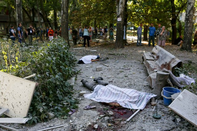Local residents and journalists look at bodies of victims killed by what locals say was recent shelling by Ukrainian forces in Donetsk August 23, 2014. (Photo by Maxim Shemetov/Reuters)