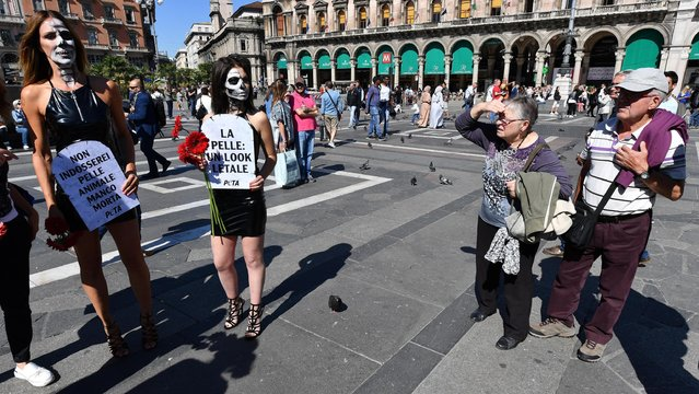"""An elderly couple looks at animal rights activists, including musician Kris Reichert, left, hold up signs with writing in Italian reading """"Leather: a lethal look"""" and """"I wouldn't wear animal skin even if I were dead"""" as they stage a demonstration in front of Milan's Duomo gothic cathedral, Italy, Wednesday, September 20, 2017. (Photo by Luca Bruno/AP Photo)"""