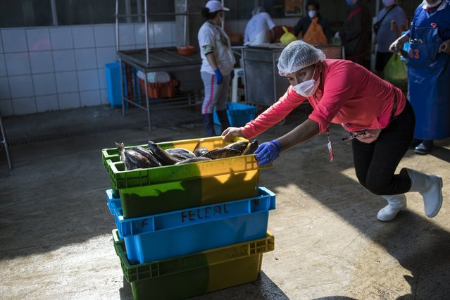 A worker, wearing a face mask as a measure against the spread of the new coronavirus, pushes crates of fish at a marine fish market in Lima, Peru, Monday, April 6, 2020. (Photo by Rodrigo Abd/AP Photo)