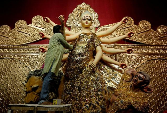 An artisan adorns a gold saree, a traditional Indian women cloth, on an idol of Hindu goddess Durga, at a temporary platform called pandal, ahead of the Durga Puja festival in Kolkata, India September 23, 2017. (Photo by Rupak De Chowdhuri/Reuters)