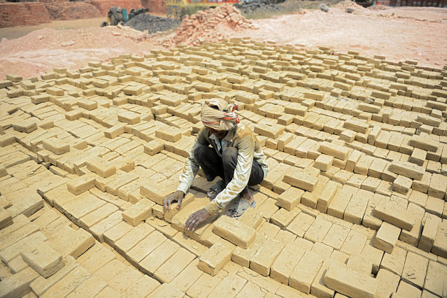 A labourer works at a brick kiln after the government eased a nationwide lockdown imposed as a preventive measure against the spread of the COVID-19 coronavirus, in Allahabad on April 20, 2020. (Photo by Sanjay Kanojia/AFP Photo)