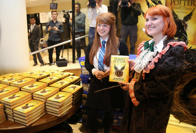 Competition winner Fran Plagge (R) is the first to receive a copy of the book of the play of Harry Potter and the Cursed Child parts One and Two at a bookstore in London, Britain July 31, 2016. (Photo by Neil Hall/Reuters)