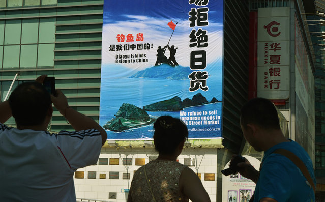 Onlookers view a large protest banner at the Silk Street market, which is famous for selling counterfeit designer brand goods, as anti-Japanese protests continue in Beijing over the Diaoyu/Senkaku Islands issue, on September 17, 2012. (Photo by Mark Ralston/AFP Photo)