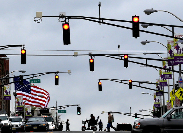 A  flag waves in gusty winds as pedestrians cross the street  in Newark, New Jersey, on September 18, 2012. A tornado watch was issued for parts of New Jersey, New York City and New York's lower Hudson Valley. (Photo by Julio Cortez/Associated Press)