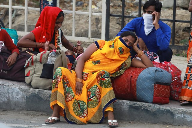Migrant workers are seen waiting as they were stopped from crossing the border to their home state of Uttar Pradesh, during an extended nationwide lockdown to slow the spread of the coronavirus disease (COVID-19), in New Delhi, India, May 14, 2020. (Photo by Anushree Fadnavis/Reuters)