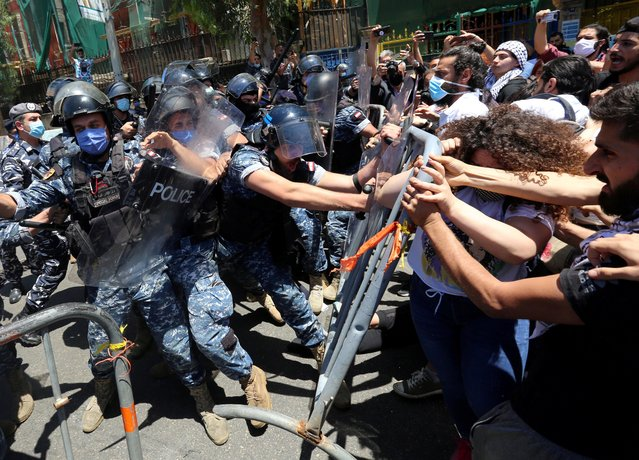 Demonstrators confront with riot police as they try to cross barricades on a road leading to the UNESCO Palace where Lebanon's parliament is holding a legislative session, during a protest against a controversial amnesty draft law, in Beirut Lebanon on May 28, 2020. (Photo by Aziz Taher/Reuters)