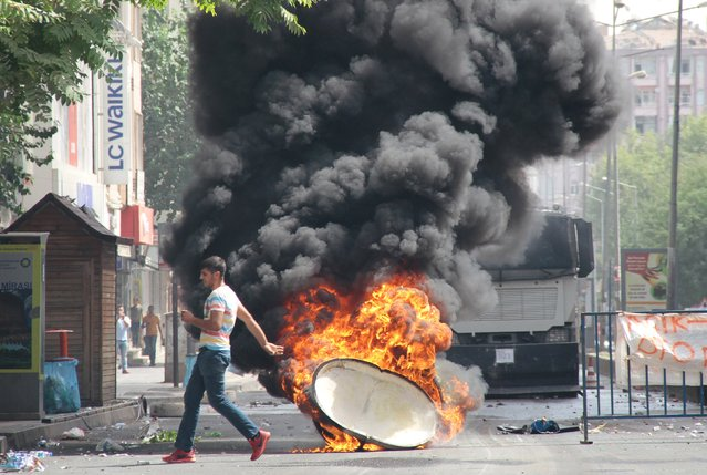 A man runs past a burning trash can, set on fire by protesters before a police vehicle, in the Kurdish dominated southeastern city of Diyarbakir, Turkey, September 13, 2015. (Photo by Sertac Kayar/Reuters)