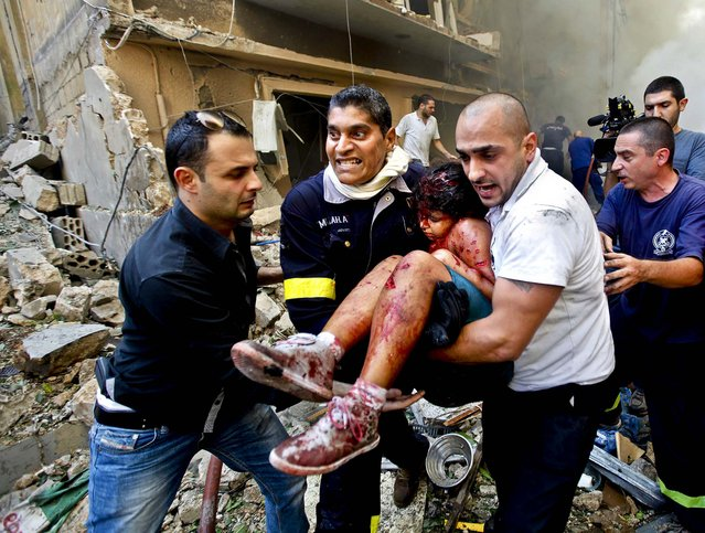 Rescue workers and civilians carry an injured girl from the scene of an explosion in the mostly Christian neighborhood of Achrafiyeh, Beirut, Lebanon October 19, 2012. (Photo by Hussein Malla/Associated Press)