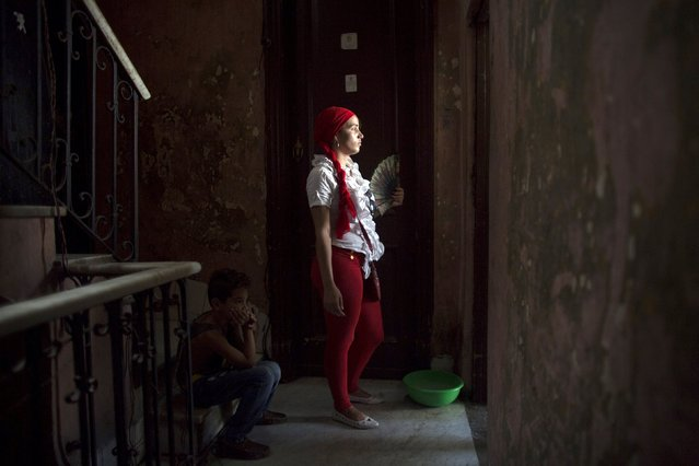 Santeria practitioner Adriana Millarez, 26, gets some fresh air during a ceremony to attract spirits of dead ancestors to ask for guidance in downtown Havana, August 18, 2015. (Photo by Alexandre Meneghini/Reuters)