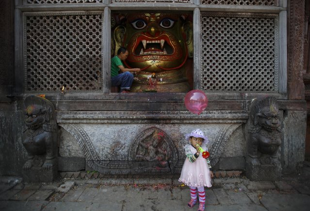 """A child stands in front of an idol of Bhairab, as a priest offers prayers during the """"Dashain"""", Hinduism's biggest religious festival in Kathmandu October 3, 2014. (Photo by Navesh Chitrakar/Reuters)"""