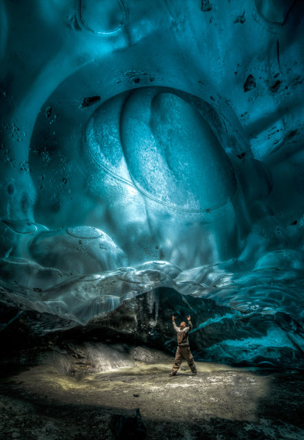 Ron Giles friend Jacob looks up into the moulon, a hole that leads straight up to the surface and is created by melting water pouring down to floor of the glacier. (Photo by Ron Gile/Caters News)