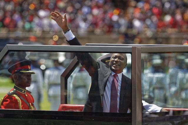 Kenyan President Uhuru Kenyatta waves from behind bulletproof glass as he arrives for his inauguration ceremony at Kasarani stadium in Nairobi, Kenya Tuesday, November 28, 2017. (Photo by Ben Curtis/AP Photo)