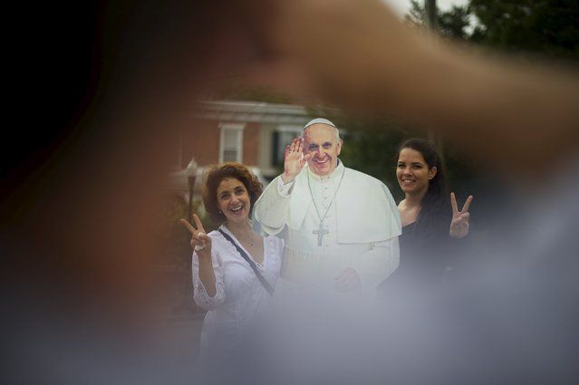 Christa Scalies, (L) the co-creator of the Pop-Up Pope, poses for a photo next to a cardboard cut-out of Pope Francis (C) with Kaitlin Repella, 21, in Wilmington, Delaware, September 19, 2015. (Photo by Mark Makela/Reuters)