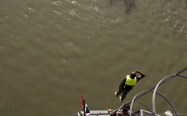 "An Iraqi army cadet performs ""the leap of faith"" from a bridge in Baghdad, September 22, 2015. (Photo by Ahmed Saad/Reuters)"