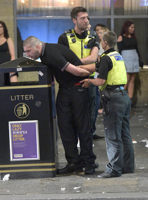 A partygoer vomits on a bin as he is restrained by police officers. Mayhem hits the streets of Newcastle, UK as clubbers out on the Toon have a little too much to drink as they enjoy the Bank Holiday on August 29, 2016. Photographs take last night show scantily-clad women passed out on the pavement, while boozed-up men were caught arguing with police. (Photo by XposurePhotos.com)