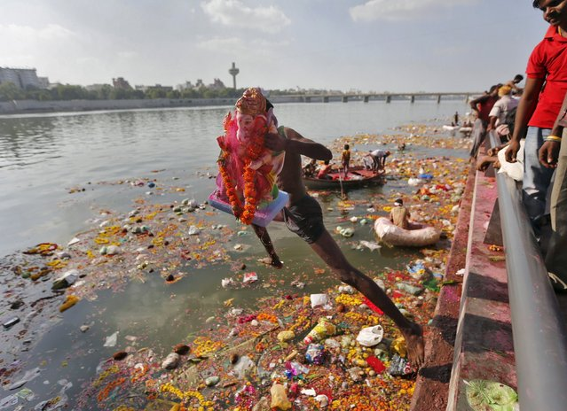 A devotee carrying an idol of the Hindu god Ganesh, the deity of prosperity, jumps into the Sabarmati river to immerse the idol on the last day of the 10-day-long Ganesh Chaturthi festival in Ahmedabad, India, September 27, 2015. (Photo by Amit Dave/Reuters)