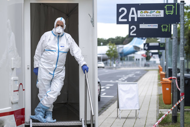 A person in protective clothes stand in the entrance of test station for the coronavirus at Cologne/Bonn Airport in Cologne, Germany, Saturday, July 25, 2020. Free corona tests for returnees from countries designated as risk areas have begun at the German airports in Düsseldorf, Cologne / Bonn and Dortmund. (Photo by Marius Becker/dpa via AP Photo)