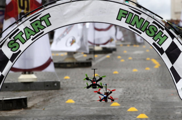 Drones cross the start and finish line during a race in Paris, Sunday, September 4, 2016. The city is hosting its first Drone Festival on Sunday, including a race along the Champs-Elysees. Drones of varying shapes and sizes are zipping along the avenue, lined with trees and luxury stores, in a circuit that stops just shy of the Arc de Triomphe. (Photo by Christophe Ena/AP Photo)