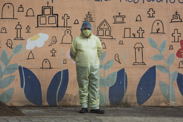 Funeral home worker Manuel Castro, wearing a full protective gear to protect himself from the spread of the new coronavirus, waits to enter La Verbena cemetery in Guatemala City, Wednesday, July 29, 2020. (Photo by Moises Castillo/AP Photo)