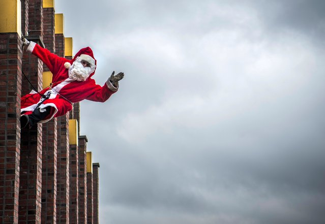 A man dressed as Father Christmas aka Santa Claus poses on the top of the Kollhoff tower in front of a Berlin skyline, on December 17, 2017 as part of a yearly stunt before the festive season. (Photo by John MacDougall/AFP Photo)