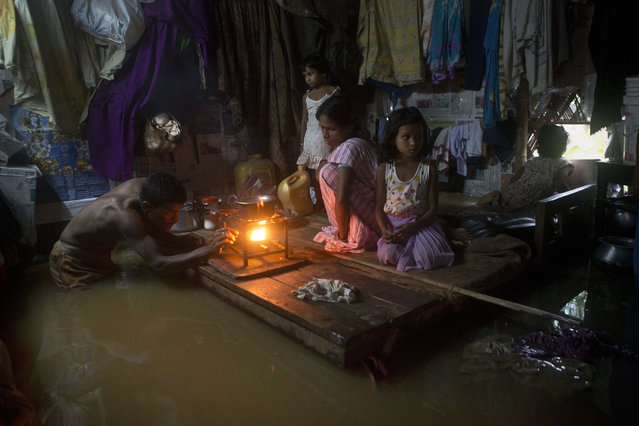A man lights a stove to make food as his family members take shelter on a bed after flood waters enter their house following heavy monsoon rains in Gauhati, India, Wednesday, September 23, 2015. India receives its monsoon rains from June to September. (Photo by Anupam Nath/AP Photo)