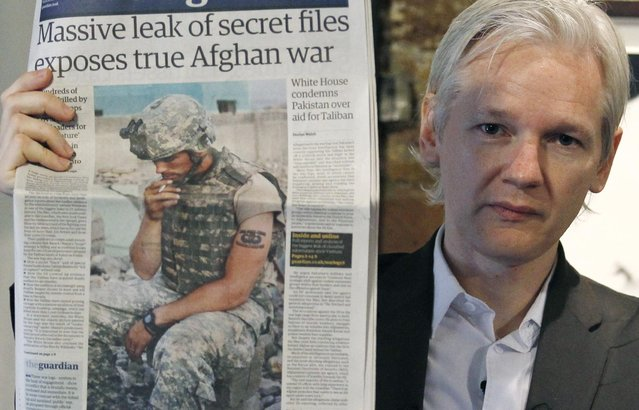 Wikileaks founder Julian Assange holds up a copy of a newspaper during a press conference at the Frontline Club in central London, July 26, 2010. Thousands of leaked U.S. military documents from Afghanistan contain evidence of possible war crimes that must be urgently investigated, the founder of the whistleblowing website that published the papers said. (Photo by Andrew Winning/Reuters)