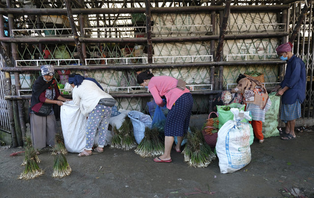 Naga women hold sacks containing local vegetables at a market early morning in Kohima, capital of the northeastern Indian state of Nagaland, Tuesday, June 30, 2020. Several Indian states have reimposed partial or full lockdowns to stem the spread of the coronavirus. (Photo by Yirmiyan Arthur/AP Photo)