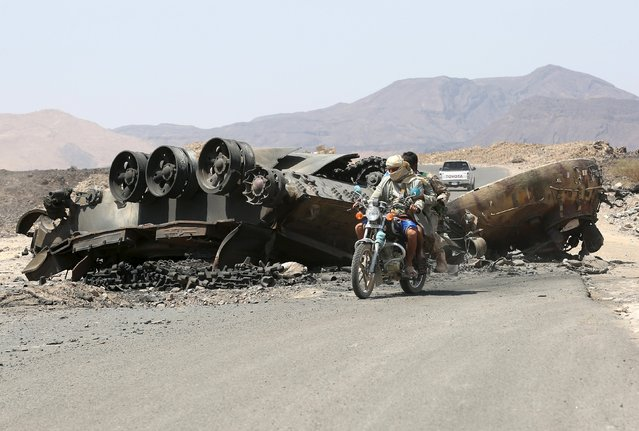 Tribal fighters loyal to Yemen's government ride a motorcycle as they pass by a destroyed tank on the side of the road at the frontline of fighting against Houthi militants in the central province of Marib October 8, 2015. (Photo by Reuters/Stringer)