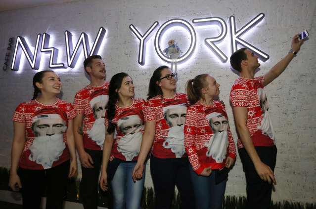 """Waiters, marking the holiday season and wearing T-shirts with an image of Russian President Vladimir Putin dressed as Santa Claus, pose for a picture at the """"New York"""" coffee bar in central Krasnoyarsk, Russia January 12, 2018. (Photo by Ilya Naymushin/Reuters)"""